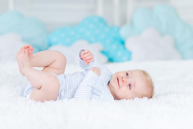 Gelukkige baby op het bed op zijn rug glimlachend, babyjongen blond zes maanden oud