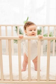 Gelukkige baby toont tong terwijl hij in de wieg staat