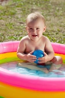 Gelukkige baby zwemmen in opblaasbaar zwembad