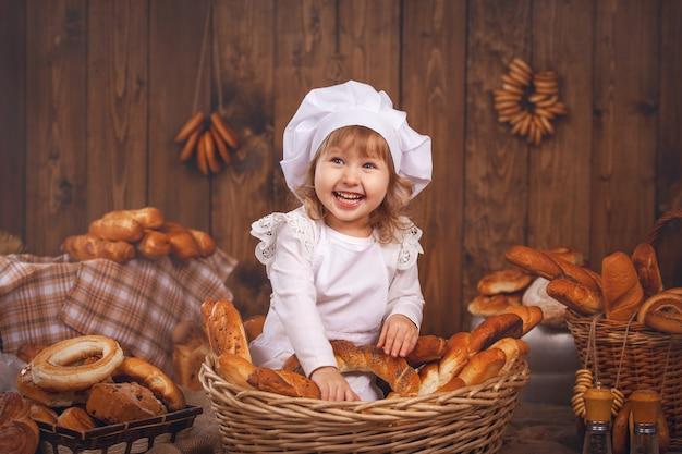 Gelukkige babychef-kok in rieten mand lachende speelchef-kok
