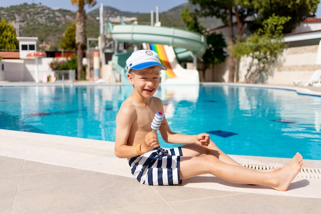 Gelukkige babyjongen bij het zwembad met glijbanen die ijs eten in de zomer, het concept van een zomervakantie aan zee en vakantie