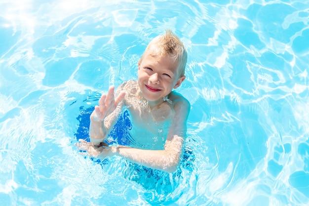Gelukkige babyjongen die in het blauwe waterzwembad zwemt, het concept van zomervakanties en schoolvakanties