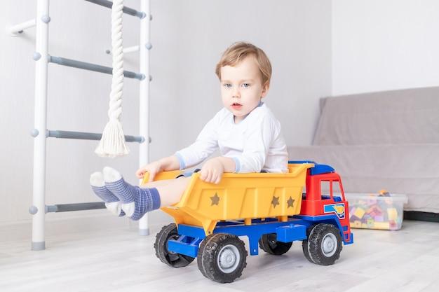 Gelukkige babyjongen die thuis speelt, in een typemachine rijdt, het concept van een kinderspel