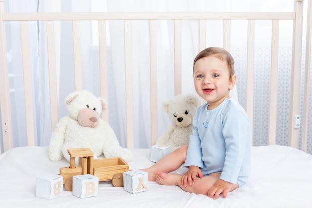 Gelukkige babyjongen in een wieg in de kinderkamer met een houten speelgoed dat lacht of lacht op een katoenen wit bed