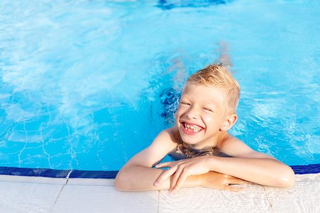 Gelukkige babyjongen in het zwembad met blauw water baden en glimlachen, het concept van zomervakantie en reizen