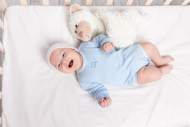 Gelukkige babyjongen in wieg met teddybeerstuk speelgoed, kinderen en geboorteconcept