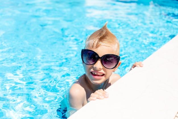 Gelukkige babyjongen in zonnebril in een blauw waterzwembad, het concept van zomervakantie en reizen