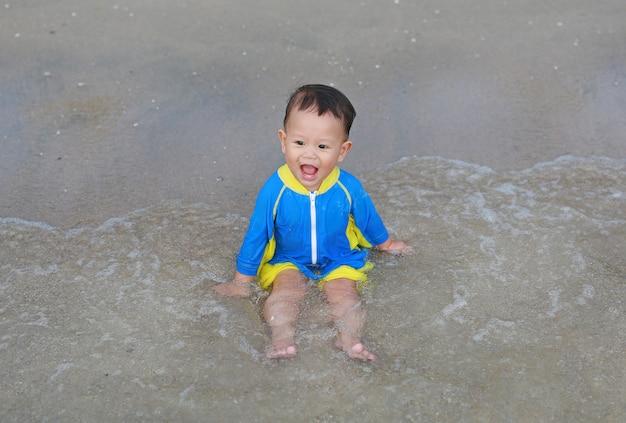 Gelukkige babyjongen in zwemmend kostuum die pret spelen overzeese golven en water op het strand hebben.