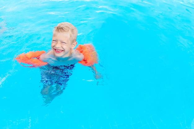 Gelukkige babyjongen zwemt of leert zwemmen in het blauwe waterzwembad in armbanden, het concept van zomervakanties en schoolvakanties