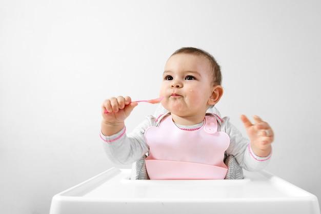 Gelukkige babypeuter als hoge voorzitter met lepel in zijn hand