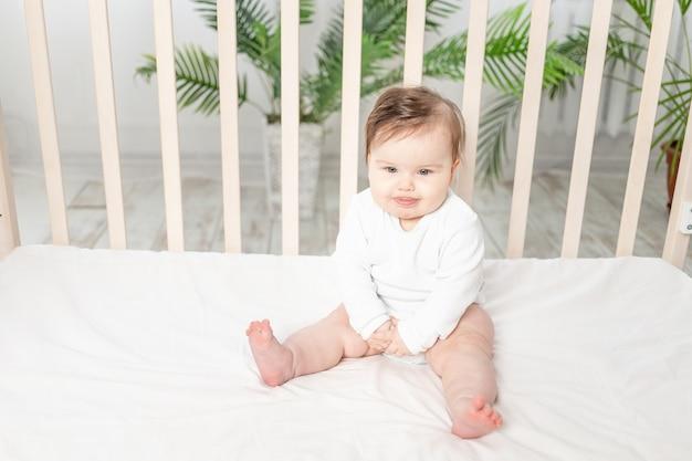 Gelukkige babyzitting in een wieg in een witte romper