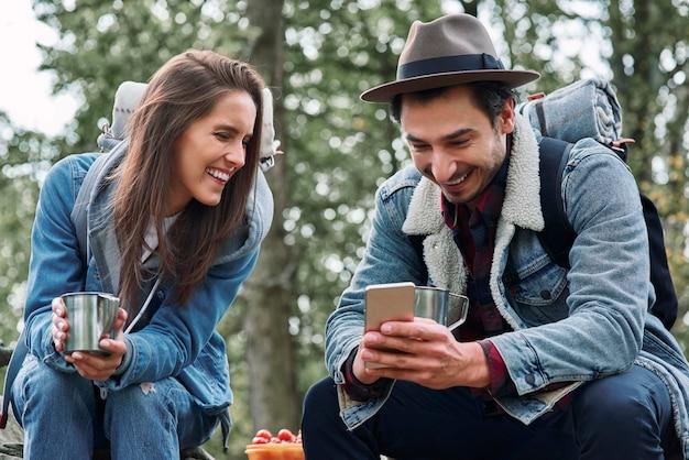 Gelukkige backpackers die koffie drinken en mobiele telefoon gebruiken