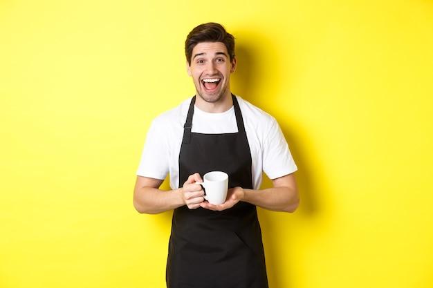 Gelukkige barista die in zwarte schort koffiekop houdt, lacht en zich over gele achtergrond bevindt.