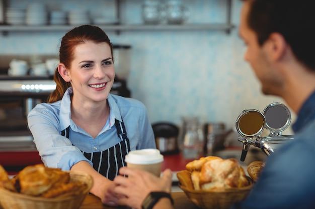 Gelukkige barista die koffie aanbieden aan klant bij koffie