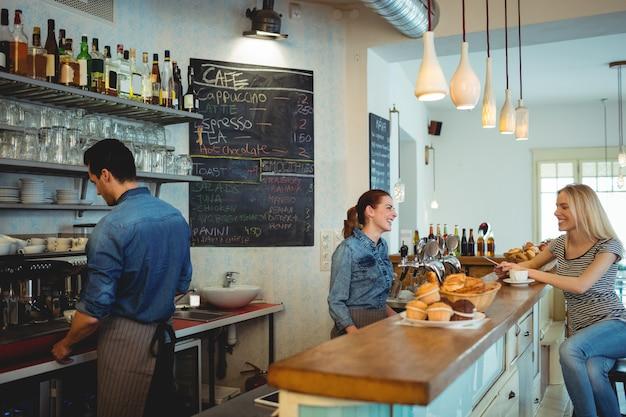 Gelukkige barista die met klant bij cafetaria communiceren
