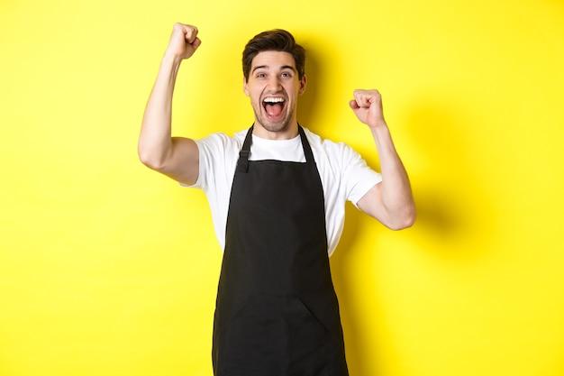 Gelukkige barista die overwinning viert, handen opheft en schreeuwt van vreugde, zwarte schort draagt, winkeluniform, staande tegen gele achtergrond.