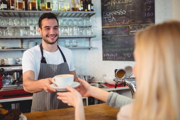 Gelukkige barista dienende koffie aan vrouw bij koffie