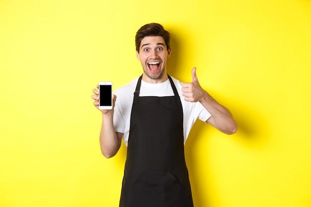 Gelukkige barista in zwart schort met smartphonescherm, duim-omhoog, cafétoepassing aanbevelen, staande over gele muur