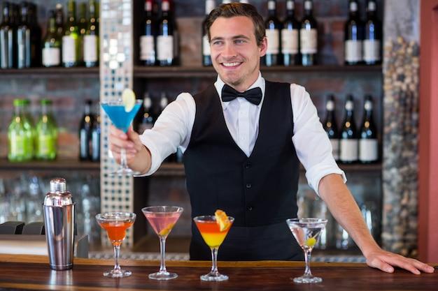 Gelukkige barman die een blauwe martini dient