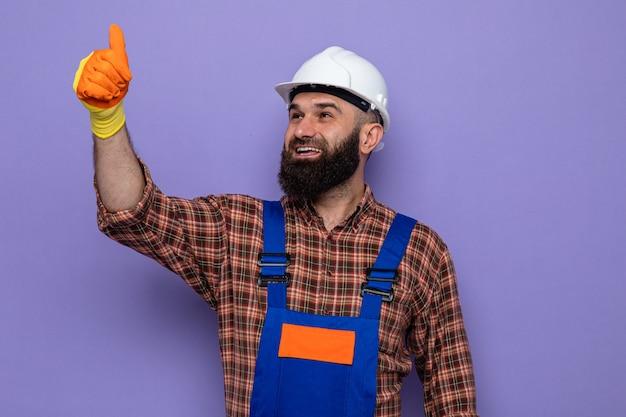 Gelukkige, bebaarde bouwman in bouwuniform en veiligheidshelm met rubberen handschoenen die omhoog lacht en vrolijk duimen laat zien