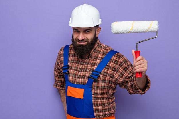 Gelukkige bebaarde bouwman in bouwuniform en veiligheidshelm met verfroller die vrolijk lacht