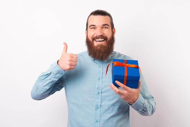 Gelukkige bebaarde man toont duim terwijl hij een geschenkdoos vasthoudt.