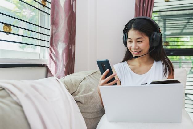 Gelukkige bedrijfs aziatische vrouw die mobiele telefoon en laptop voor het werk van huis met behulp van
