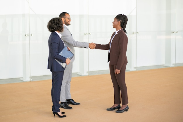 Gelukkige bedrijfscollega's die elkaar verwelkomen