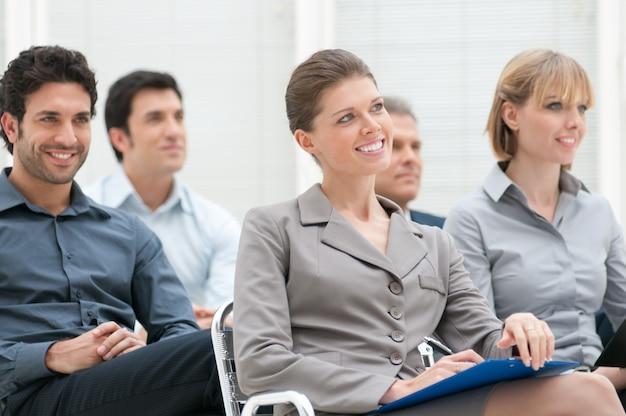 Gelukkige bedrijfsgroep die een educatieve vergaderingsconferentie bijwoont