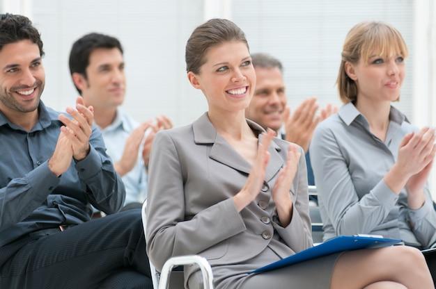 Gelukkige bedrijfsgroep mensen die handen klappen tijdens een vergaderingsconferentie