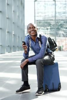 Gelukkige bedrijfsmens die bij station met bagage en cellphone wacht