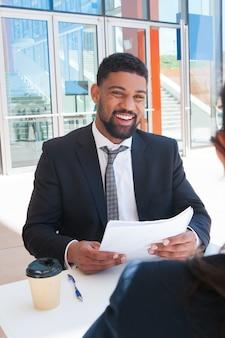 Gelukkige bedrijfsmens die documenten bespreken met partner in koffie
