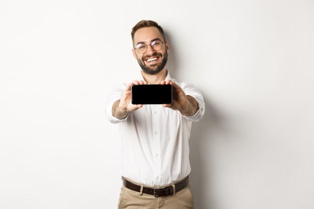 Gelukkige bedrijfsmens die mobiel scherm toont, telefoon horizontaal houdt, tevreden staand