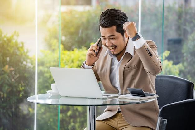 Gelukkige bedrijfsmens die op mobiele telefoon spreekt en laptop met behulp van