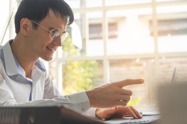 Gelukkige bedrijfsmens die vinger op laptop het scherm richt
