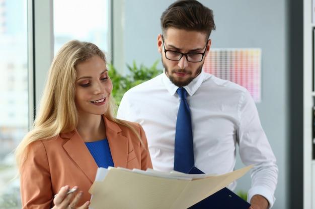 Gelukkige bedrijfsmensen die documenten samen bekijken