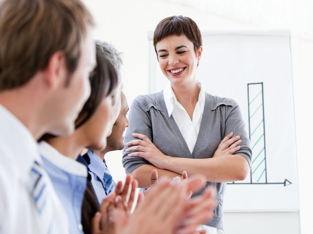 Gelukkige bedrijfsmensen die een goede presentatie toejuichen