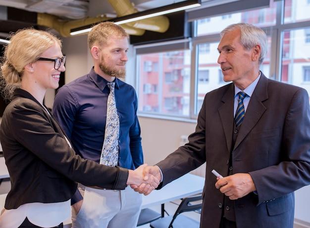 Gelukkige bedrijfsmensen die handen na het eindigen van een vergadering schudden
