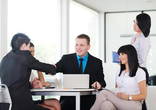 Gelukkige bedrijfsmensen die handen op een overeenkomst schudden en over werkende lijst glimlachen