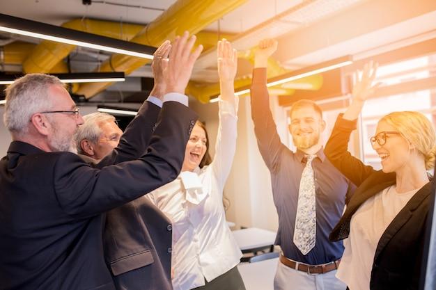 Gelukkige bedrijfsmensen die hun succes in het bureau vieren