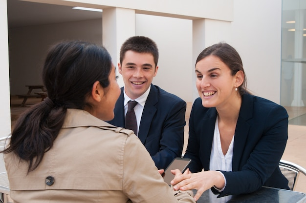 Gelukkige bedrijfsmensen en klant die bij bureau in openlucht spreken