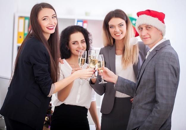 Gelukkige bedrijfsmensen in kerstmanhoeden bekijken camera en glimlachen terwijl het vieren van nieuwjaar