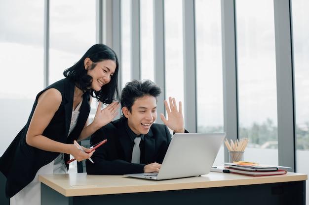 Gelukkige bedrijfsmensen met duimen omhoog op videogesprek met laptop op kantoor