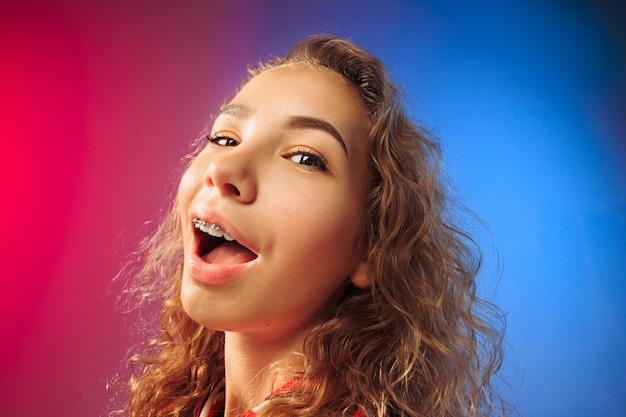 Gelukkige bedrijfsvrouw die en op rode en blauwe studioachtergrond bevindt zich glimlacht. mooi vrouwelijk portret van halve lengte. jonge emotionele vrouw. de menselijke emoties, gezichtsuitdrukking concept