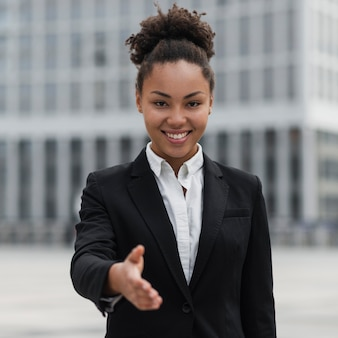 Gelukkige bedrijfsvrouw die hand toont