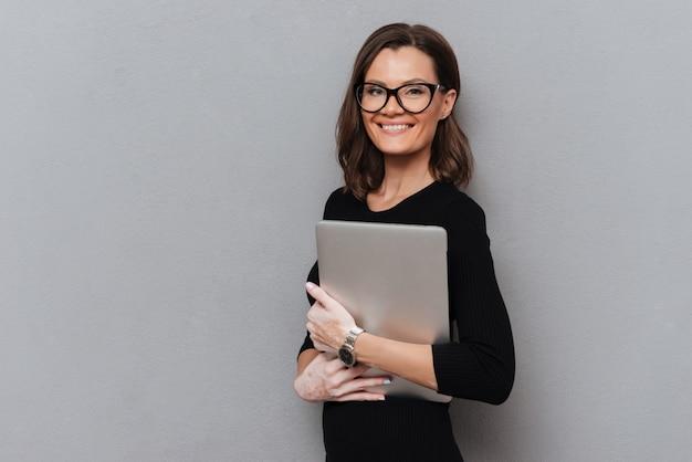 Gelukkige bedrijfsvrouw die in oogglazen tabletcomputer houden