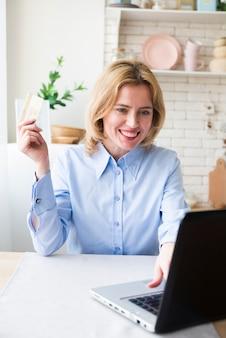 Gelukkige bedrijfsvrouw die laptop en creditcard met behulp van