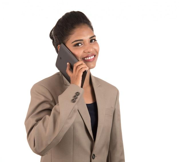 Gelukkige bedrijfsvrouw die op de mobiele telefoon of smartphone spreekt die op witte ruimte wordt geïsoleerd