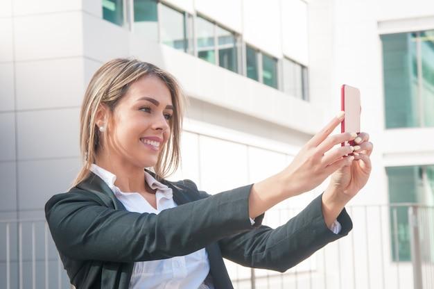 Gelukkige bedrijfsvrouw die selfie foto in openlucht spreken