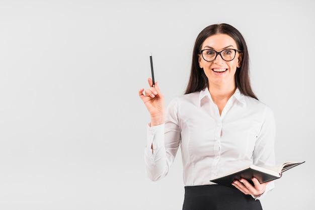 Gelukkige bedrijfsvrouw die zich met notitieboekje bevindt